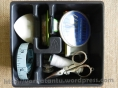 Sewing tools case filled with marking chalk, measuring tape, hand needles, machine needles, ball pins, needle threader, bobbin, thread spool and small scissors.